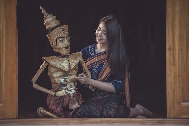 Thaise vrouw die traditionele marionet gebruikt
