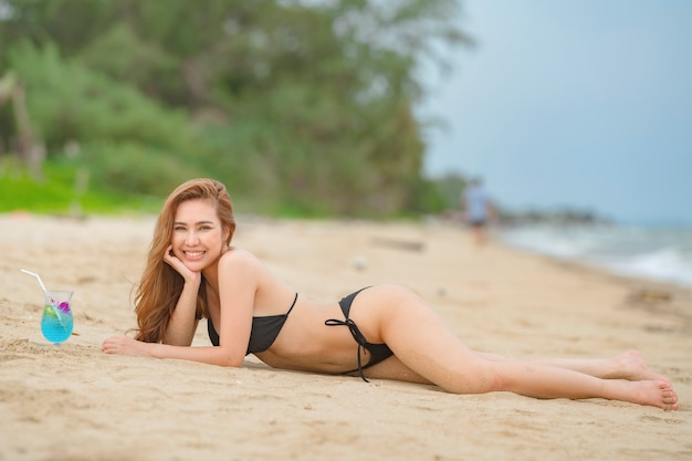 Thaise vrouw, gekleed in zwarte bikini poseren in het strand