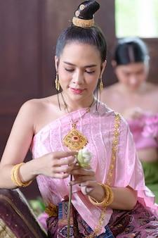 Thaise vrouwen in thaise traditionele kleding versieren bloemen.