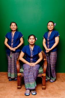 Thaise vrouwenmasseurs in tradiotionalklerenportret op groene achtergrond.