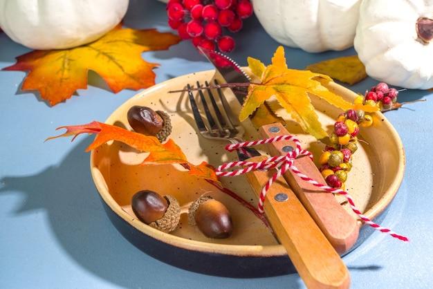 Thanksgiving-dagtafel, bestek (bord, mes, vork) en servet met decoratie op blauwe tafel, bovenaanzicht kopieerruimte