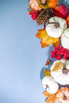 Thanksgiving day, halloween feestelijke geetiing-kaart met pompoenen, decoratieve bessen en herfstbladeren op turkooisblauwe tafelkopieerruimte. herfstvakantie flatlay kopieerruimte