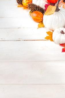 Thanksgiving day, halloween feestelijke geetiing-kaart met pompoenen, decoratieve bessen en herfstbladeren op witte houten tafel kopieerruimte. herfstvakantie flatlay kopieerruimte