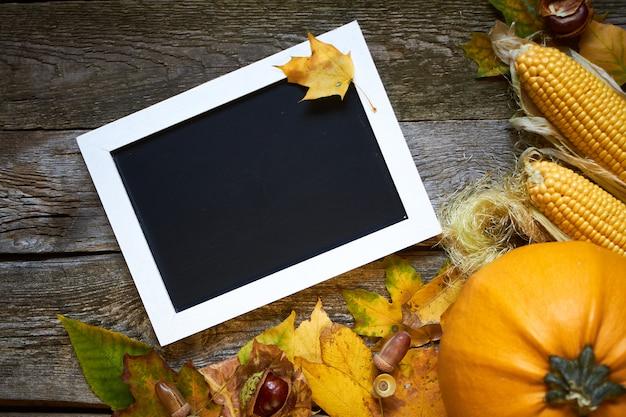 Thanksgiving herfst, houten oppervlak met pompoenen, verdorde bladeren, eikels, kastanjes en een frame voor inscripties