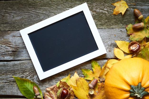 Thanksgiving herfst thema. pompoenen, verdorde bladeren, eikels, kastanjes en een frame voor inscripties