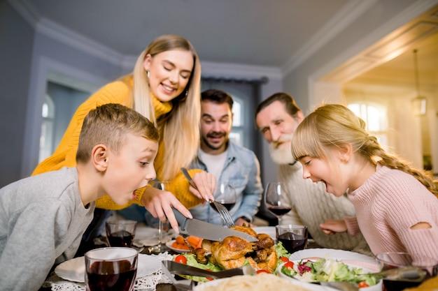 Thanksgiving viering traditie familie diner concept. de grappige foto van grote familiezitting bij de lijst, moeder snijdt turkije en twee kleine opgewekte kinderen die het voedsel bekijken