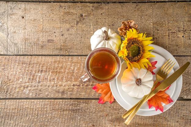 Thanksgiving voedsel concept. herfsttafel met bord, theekop, pompoenen, zonnebloem en warme plaid of trui, comfort en gezellige bakstenen houten thuisachtergrond kopie ruimte