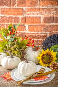 Thanksgiving voedsel concept. herfsttafel met bord, theekop, pompoenen, zonnebloem en warme plaid of trui, comfort en gezellige bakstenen houten thuismuur kopie ruimte