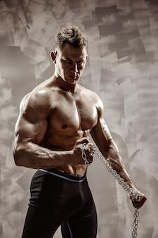 The perfect mannelijk lichaam - awesome bodybuilder poseren. houd een ketting met tatoeage vast