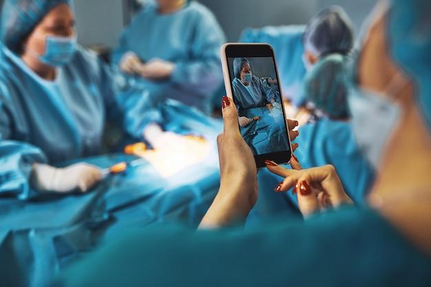 Theater voor chirurgie. de assistent voert een online uitzending uit van een complexe operatie. moderne technologie, moderne geneeskunde.
