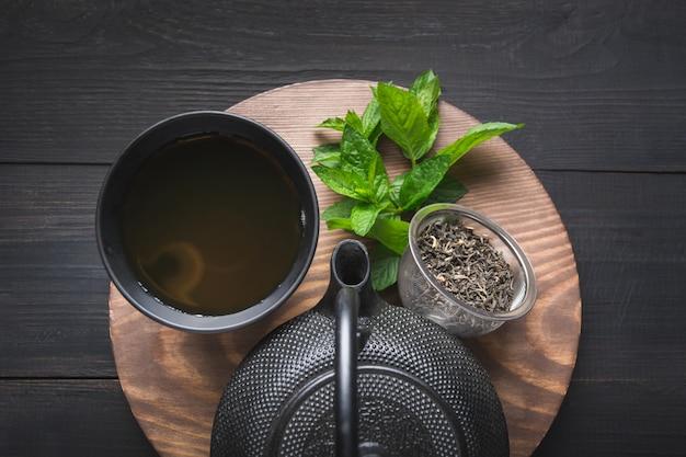 Thee ceremonie. kop theeën met melissa en ketel op donkere achtergrond. chinees thee concept. uitzicht van boven.