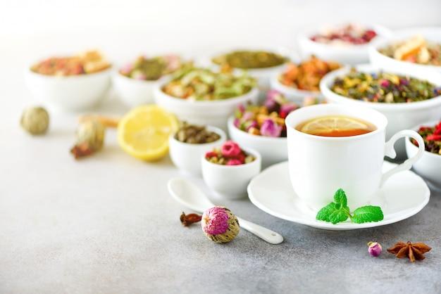 Thee concept met kopie ruimte. verschillende soorten droge thee in witte ceramische kommen en kop aromatische thee op grijze achtergrond.