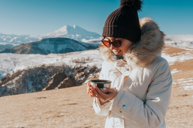 Thee drinken in de bergen. reiziger met een mok warme drank in de bergen.