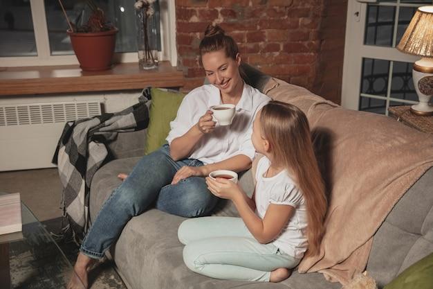 Thee drinken, praten. moeder en dochter tijdens zelfisolatie thuis in quarantaine, gezellige familietijd, comfort, huiselijk leven. vrolijke, blij lachende modellen. veiligheid, preventie, liefdesconcept.