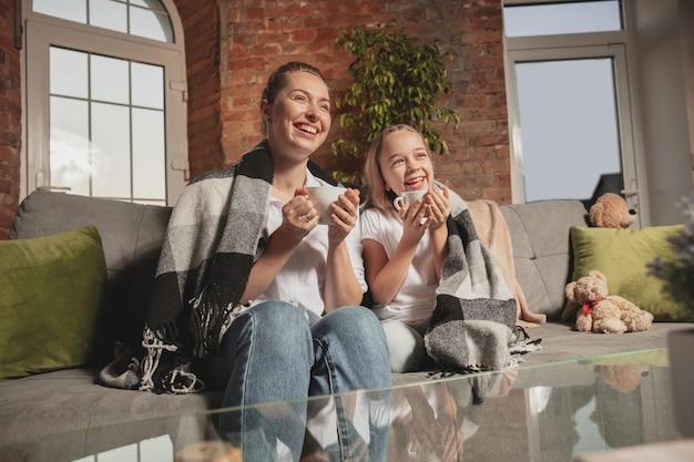 Thee drinken, praten. moeder en dochter tijdens zelfisolatie thuis in quarantaine.