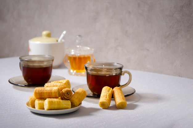 Thee drinken. twee kopjes op tafel met thee en wafels.