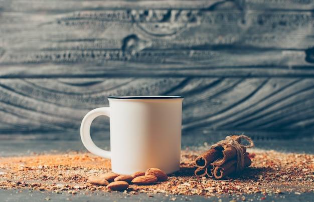 Thee en gedroogde kruiden met droge kaneel en amandel op houten tafel, zijaanzicht,