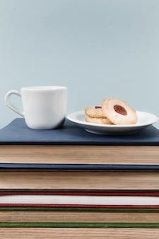 Thee en koekjes op boekstapel