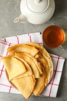 Thee en plaat van dunne pannenkoeken op grijze tafel