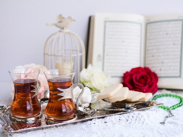 Thee en snoepjes op dienende dienblad met geopende koran op achtergrond