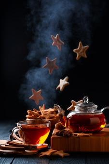 Thee en vallende sterren vormige koekjes met poedersuiker. verticale compositie op een donkere achtergrond
