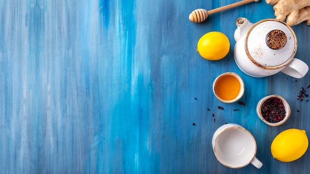Thee, honing, citroen en gember op een achtergrond in kleur. kopieer ruimte, bovenaanzicht.