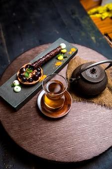 Thee in armudu-glas, chinese theepot en chocoladetartaleta
