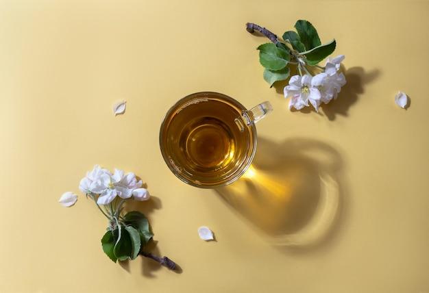 Thee in een glazen beker met bloemen van een appelboom op een gele achtergrond