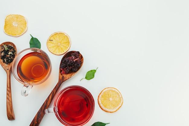 Thee in een glazen beker met specerijen en kruiden. bovenaanzicht witte achtergrond