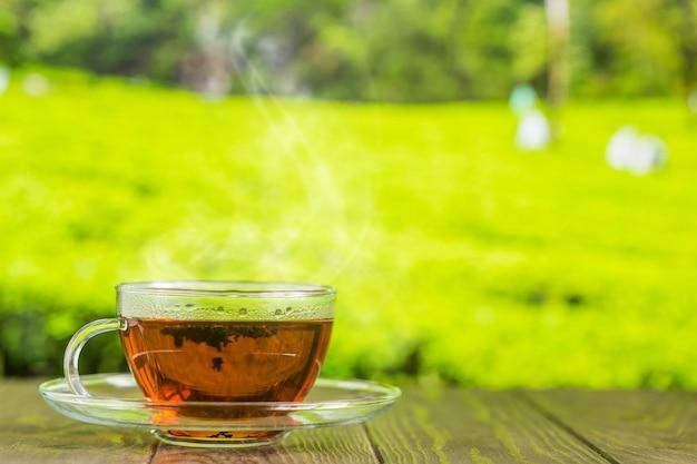 Thee in een glazen beker op de houten tafel en de theeplantages