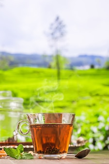 Thee in een glazen beker op de houten tafel en het oppervlak van de theeplantages