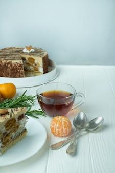 Thee in een glazen beker op een lichte houten achtergrond. zwarte thee met rozemarijn en mandarijnen. ruimte voor tekst.