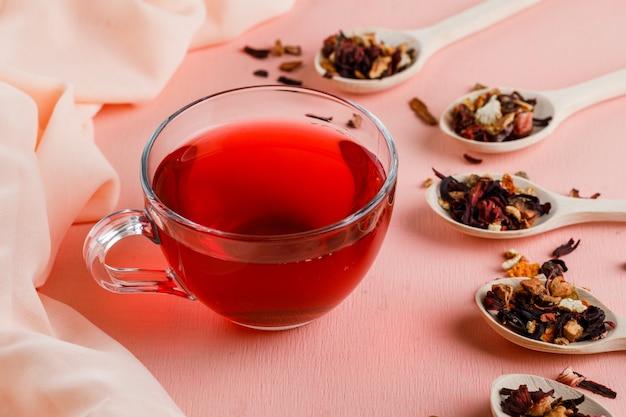 Thee in een glazen mok met gedroogde kruiden hoog op roze en textiel