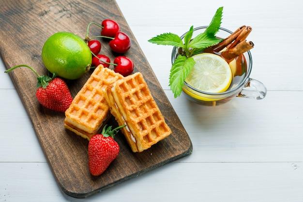 Thee in een kopje met citroen, wafel, aardbei, kers, munt, kaneel plat lag op houten en snijplank