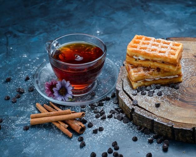 Thee in een kopje met kaneelstokjes, wafel, choco chips, bloemen, houten plank hoge hoek uitzicht op een blauwe ondergrond