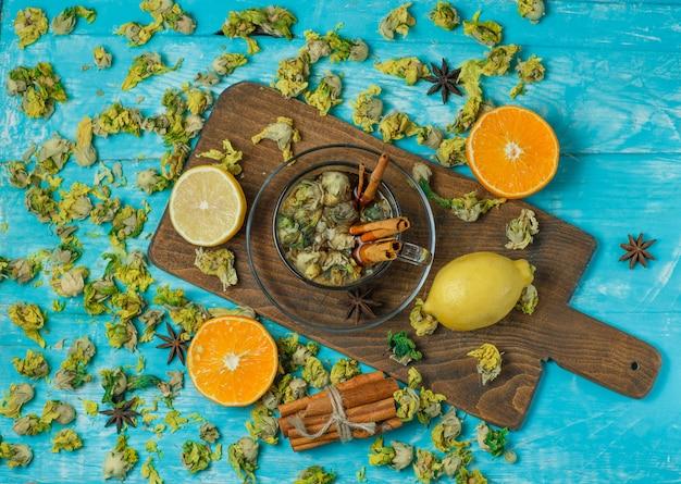 Thee in een mok met kruiden, sinaasappel, citroen, gedroogde kruiden bovenaanzicht op blauw en snijplank