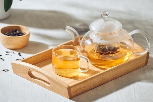 Thee in een transparante beker en theepot op een houten achtergrond