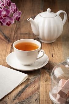 Thee in een witte keramische beker en theepot op tafel. donkere achtergrond.