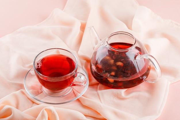 Thee in glazen mok en theepot op roze en textiel hoog.