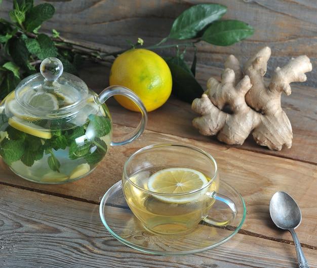 Thee in glazen mok met gemberwortel, citroen en mint met ingrediënten voor gezonde thee