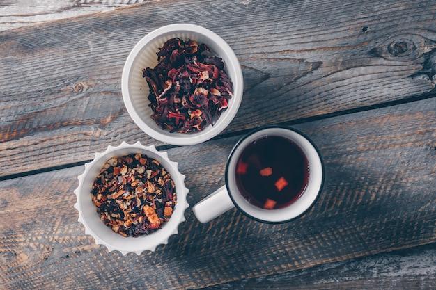 Thee in kopjes en een kom met thee kruiden bovenaanzicht op een donkere houten achtergrond