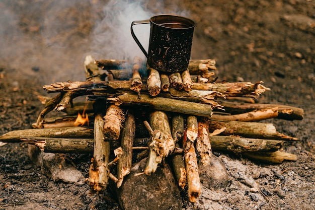 Thee in metalen mok warmt op op vreugdevuur