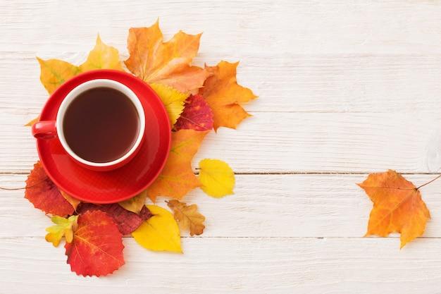 Thee in rode kop met herfst bladeren op witte tafel