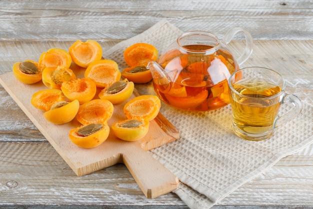 Thee in theepot en mok met abrikozen, snijplank bovenaanzicht op houten en keuken handdoek