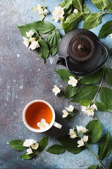 Thee jasmijn achtergrond met theepot, bladeren en bloemen op donkere textuur, bovenaanzicht, kopie ruimte, verticaal