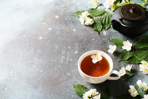 Thee jasmijn achtergrond met theepot, bladeren en bloemen op donkere textuur, bovenaanzicht, kopie ruimte