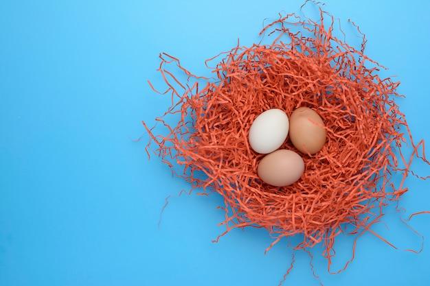 Thee kippeneieren in het nest op blauwe achtergrond. bovenaanzicht. kopieer ruimte voor tekst.