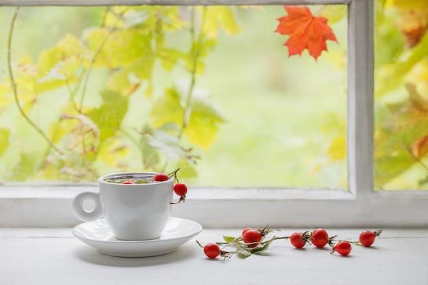 Thee met bessen van een dogrose op een vensterbank