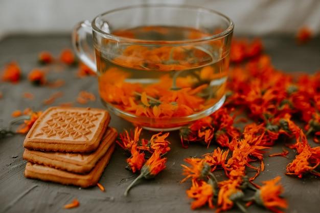 Thee met calendulabloemen en koekjes
