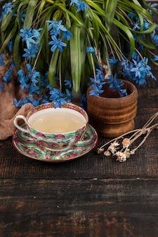 Thee met citroen en boeket van blauwe sleutelbloemen op tafel